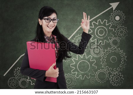 Happy businesswoman making an ok sign in front of cogwheel background - stock photo