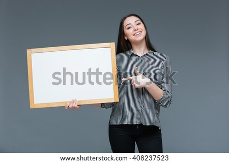 Happy businesswoman pointing finger on blank board over gray background - stock photo
