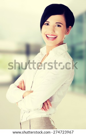Happy businesswoman posing with crossed arms - stock photo