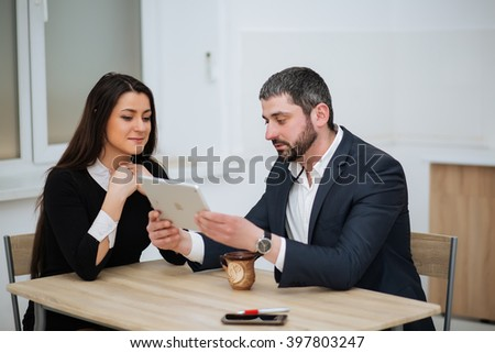 Happy Businesswoman Shaking Hands With Businessman In Office - stock photo