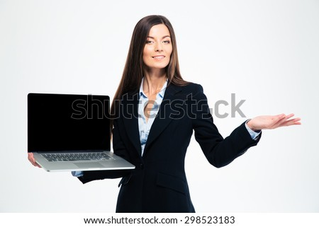 Happy businesswoman showing blank laptop screen and holding copyspace on the palm isolated on a white background. Looking at camera - stock photo