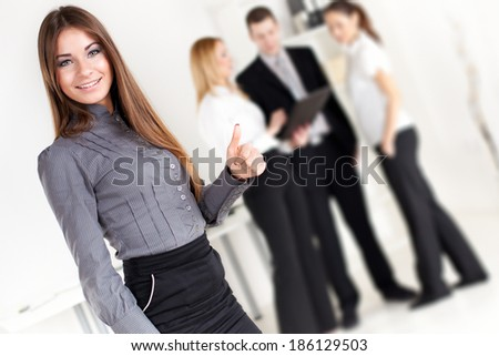 Happy Businesswoman showing thumbs up in the office. Looking at camera. Selective Focus. - stock photo