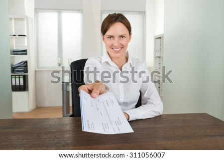 Happy Businesswoman Sitting At Desk Offering Cheque In Office - stock photo