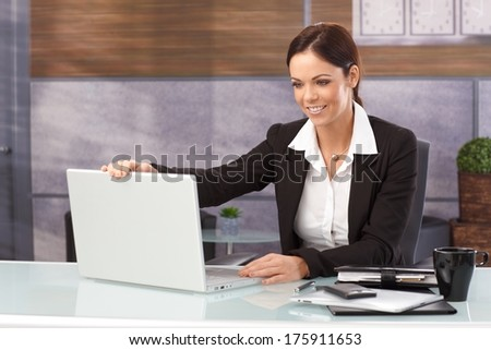 Happy businesswoman sitting at desk shutting down laptop computer, finishing work. - stock photo