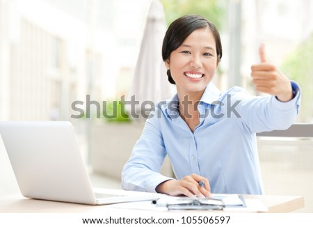 Happy businesswoman sitting at her workplace and showing thumbs up - stock photo