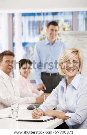 Happy businesswoman sitting at table in meeting room, looking at camera, laughing.? - stock photo