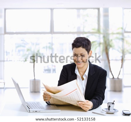 Happy businesswoman sitting at table in office lobby, reading newspaper, using laptop computer. - stock photo