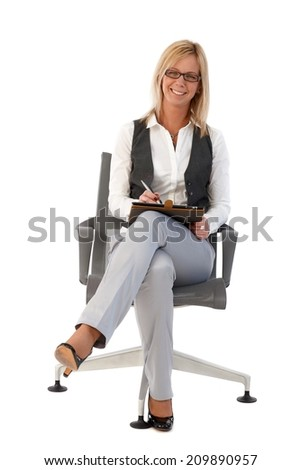 Happy businesswoman sitting in chair, using tablet, looking at camera. Full size. - stock photo