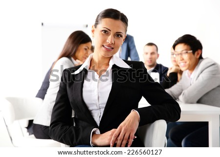 Happy businesswoman sitting in front of business meeting - stock photo