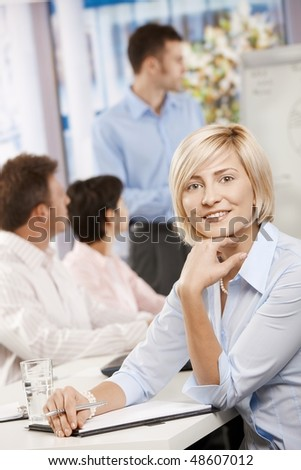 Happy businesswoman sitting on business meeting in office making notes, looking at camera smiling. - stock photo