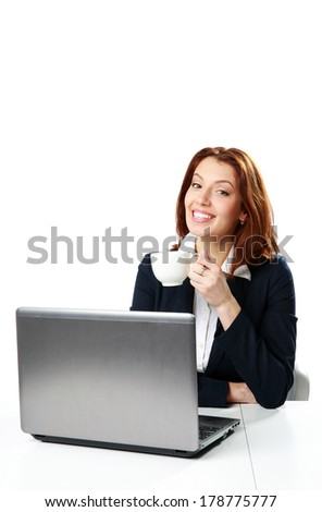 Happy businesswoman sitting on the table with laptop and drinking coffee isolated on a white background - stock photo
