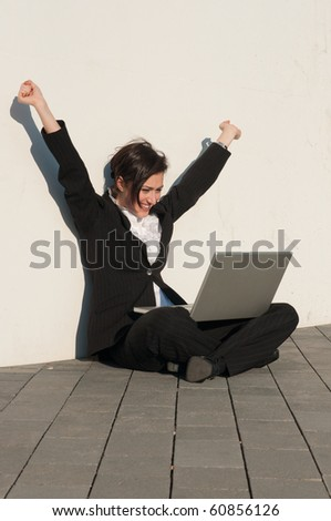 Happy businesswoman  sitting with a laptop at the wall outdoors - stock photo