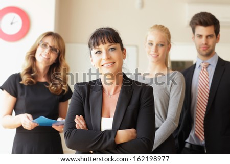 Happy businesswoman standing at office (her colleagues in the background) - stock photo
