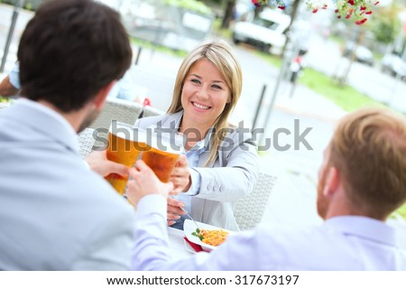 Happy businesswoman toasting beer glass with male colleagues at sidewalk cafe - stock photo