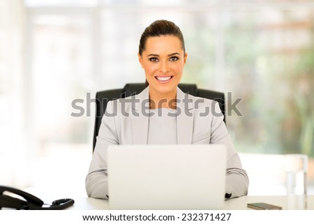 happy businesswoman using computer in office - stock photo