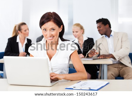 Happy Businesswoman Using Laptop In Front Of Colleagues - stock photo