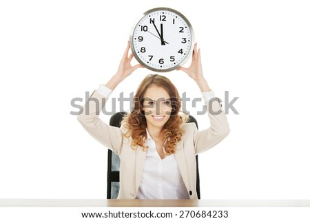 Happy businesswoman with clock by a desk. - stock photo
