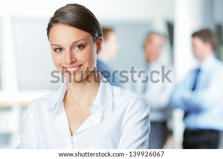 Happy businesswoman with colleagues in the background - stock photo