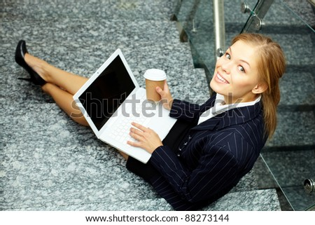 Happy businesswoman with laptop and coffee looking at camera on staircase - stock photo