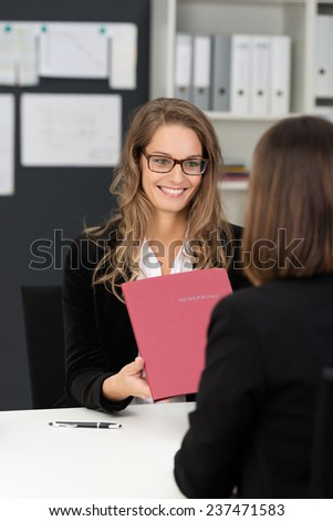 Happy Businesswoman with Long Blond Hair Giving Reports in Dark Pink Folder to her Co-worker at her Worktable. - stock photo