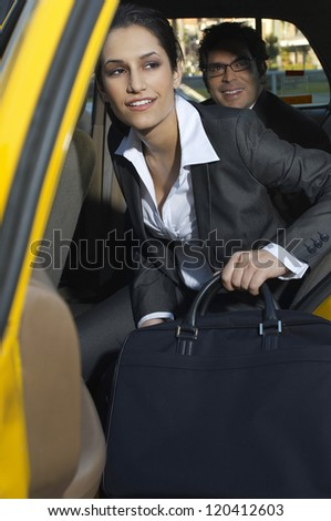 Happy businesswoman with male colleague getting out of taxi - stock photo