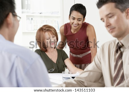 Happy businesswomen at desk with male colleagues in foreground - stock photo