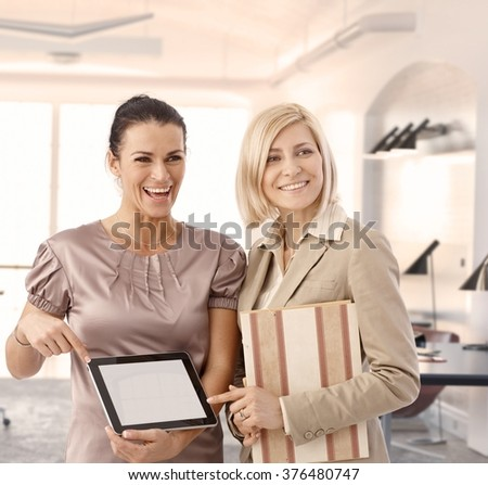 Happy businesswomen at office showing tablet, blank screen - stock photo
