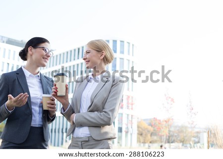 Happy businesswomen conversing while holding disposable cups outside office building - stock photo