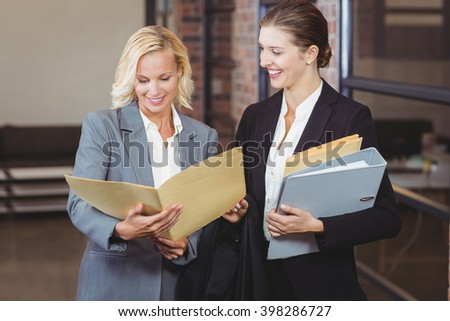 Happy businesswomen holding documents while discussing at office - stock photo