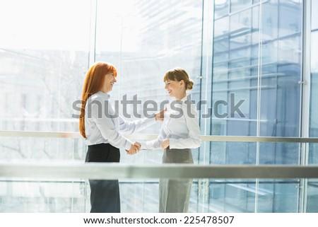 Happy businesswomen shaking hands in office - stock photo