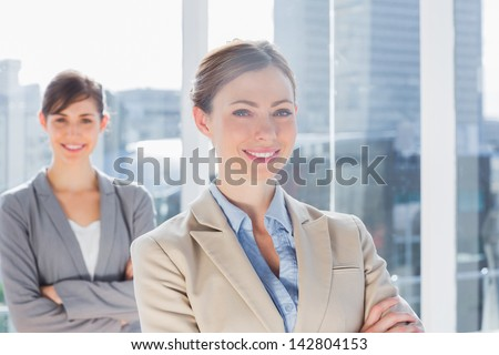 Happy businesswomen standing with arms crossed in bright office - stock photo