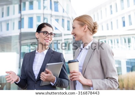 Happy businesswomen with tablet PC and disposable cup conversing outside office building - stock photo