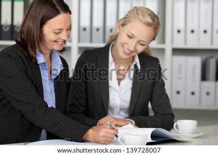 Happy businesswomen working on file at office desk - stock photo