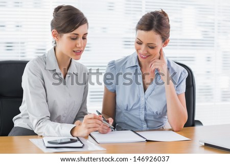 Happy businesswomen working together on documents at desk in office - stock photo