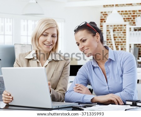 Happy businesswomen working together, using laptop, smiling. - stock photo
