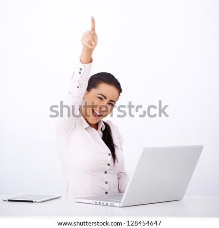 Happy businnes woman sitting at her desk, one arm rised, laptop and tablet on desk - stock photo