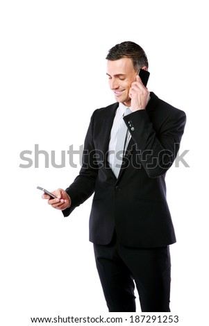 Happy busy businessman using two mobile phone over white background - stock photo