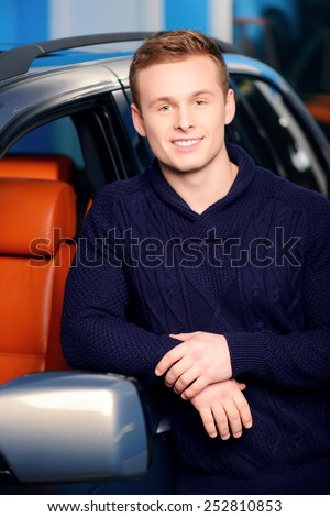 Happy car owner. Portrait of a handsome smiling man standing by his luxury car in the garage  - stock photo