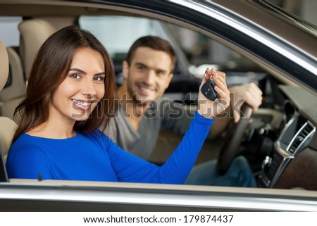 Happy car owners. Beautiful young couple sitting at the front seats of their new car while woman showing keys and smiling - stock photo