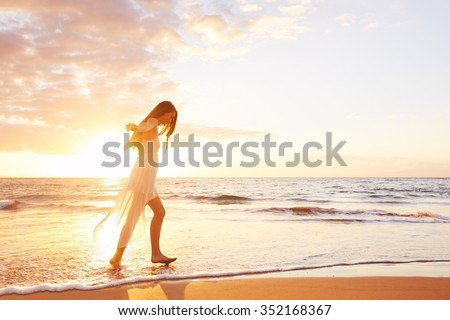 Happy carefree woman dancing at sunset on the beach. Happy free lifestyle concept. - stock photo