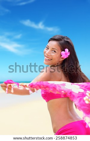 Happy carefree woman in pink bikini on Hawaiian white sand beach vacation holidays holding a scarf in the wind as freedom and relaxation concept. Exotic Asian girl wearing a Hawaii flower in the hair. - stock photo
