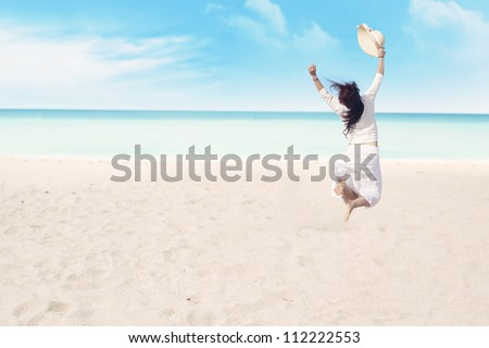 Happy carefree woman jumping on beach celebrating her freedom - stock photo