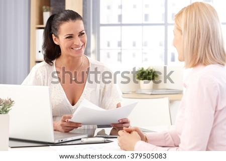 Happy casual brunette businesswoman working with laptop computer and business papers at office. - stock photo