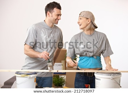 Happy casual caucasian couple at new home having fun painting. Smiling, looking at each other, standing. - stock photo