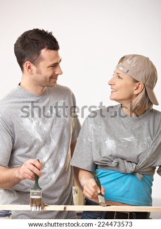 Happy casual, caucasian couple at new home looking at each other. Painting a wooden board. Smiling, having fun, standing. - stock photo