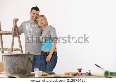 Happy casual caucasian couple standing front of painted white wall. Home renovation, new home, indoors. ladder and bucket, brush. Hugging. Smiling, looking at camera. - stock photo