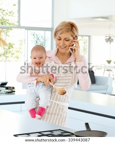 Happy, casual, caucasian housewife in kitchen with baby in hand, talking on phone. Standing, busy, cooking, wearing apron, holding wooden spoon. - stock photo