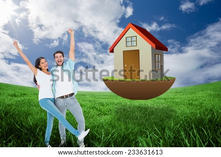 Happy casual couple cheering together against green field under blue sky - stock photo