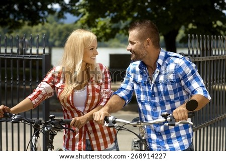 Happy casual couple on vacation with bicycle in outdoor park. Attractive blonde woman and handsome stubbly man. Smiling, sport activity, summer. - stock photo