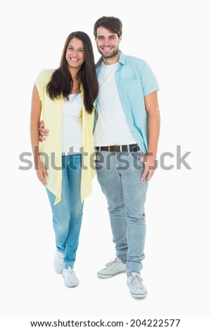 Happy casual couple smiling at camera on white background - stock photo